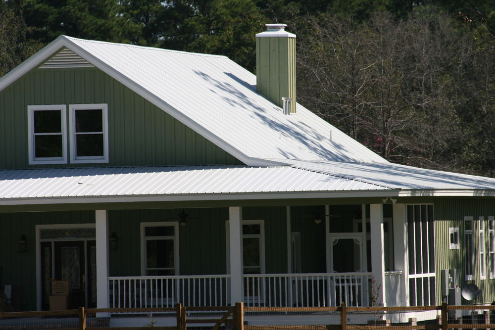 Galvalume rib roofing over a green, paneled house